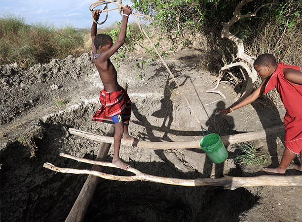 Two Tanzanian boys pull water up from a well