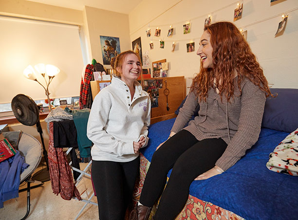 Abby Connolly '22 and Grace Acquilano '22 stand and laugh in their dorm room
