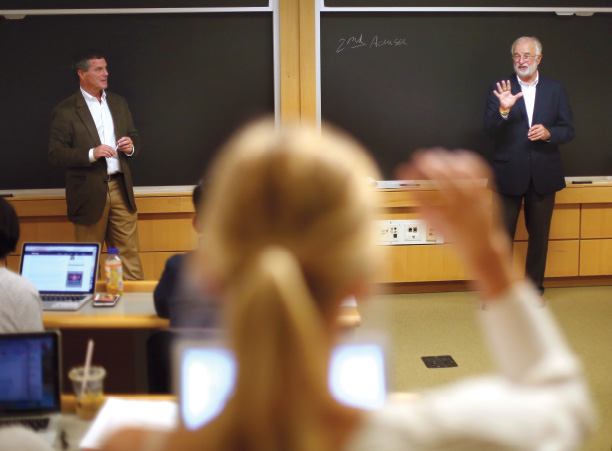 Peter Flaherty '87 and Tim Bishop '72 stand at the front of the classroom