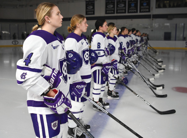 Members of the Women's Ice Hockey Team stand on the ice prior to starting a game