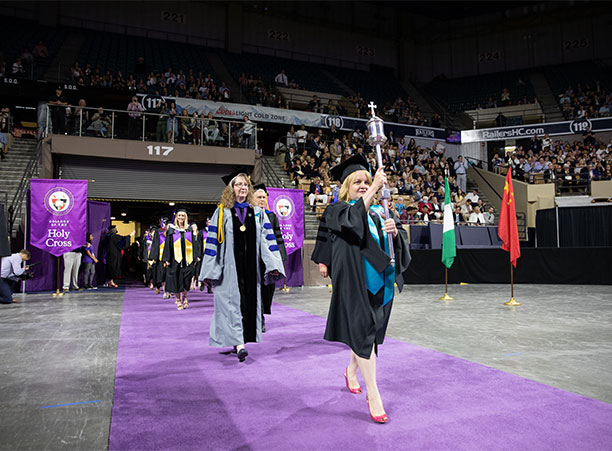 Patricia Ring, registrar, carries the college mace to lead the processional.