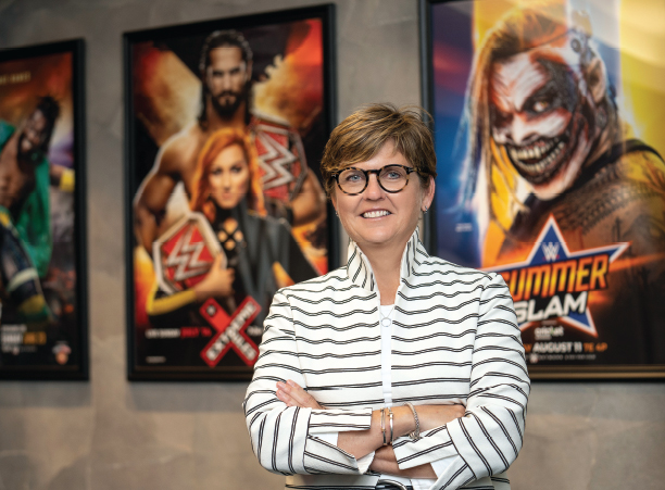 Mary Ellen Curran '86, stands in front of wrestling posters