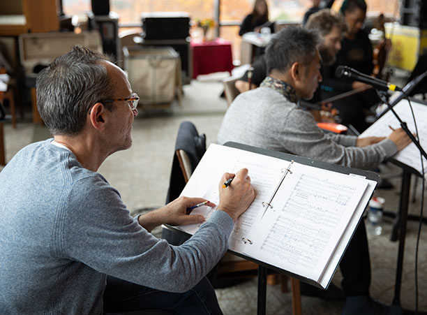 A man writes notes on a sheet of music